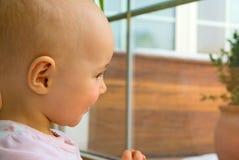 Kind, das heraus vom Fenster, Portrait schaut Stockbild