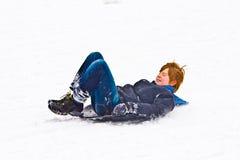 Kind, das hinunter den Hügel im Schnee sledging ist Stockfotos