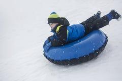Kind, das hinunter einen Hügel auf einem Schneerohr rodelt Stockfotografie