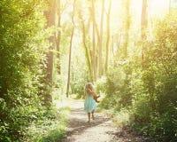 Kind, das hinunter geheimen Naturlehrpfad läuft stockfotos