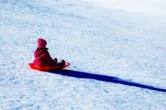 Kind, das hinunter Snowy-Hügel rodelt Stockbild