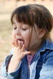 Kind, das ihre Hand leckt Lizenzfreies Stockfoto