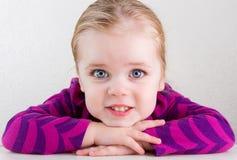 Kind, das ihren Kopf auf ihrem Handlächeln stillsteht stockbilder