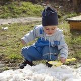 Kind, das im Frühjahr mit Schnee spielt Stockbilder
