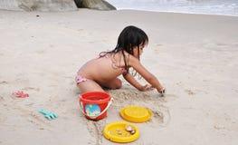 Kind, das im Sand des Strandes spielt Lizenzfreies Stockbild