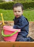 Kind, das im Sandkasten spielt Stockfoto