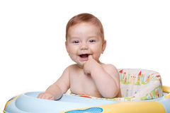 Kind, das im Schätzchenstuhl und -lächeln sitzt. Stockbild