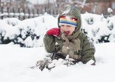 Kind, das im Schnee spielt Stockfotografie