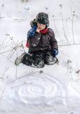 Kind, das im Schnee spielt stockfoto