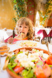Kind, das im Sommercafé isst Stockfotos