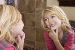 Kind, das im Spiegel fehlendem Vorderzahn betrachtet Stockfotos