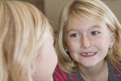 Kind, das im Spiegel fehlendem Vorderzahn betrachtet Lizenzfreies Stockbild