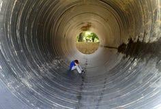 Kind, das im Tunnel und in den hinteren Bänke unter Bäumen sitzt Stockbilder