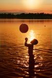 Kind, das im Wasser am Sonnenuntergang spielt Lizenzfreie Stockbilder