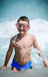Kind, das im Wasser spielt Stockbild