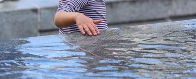 Kind, das im Wasser spielt lizenzfreie stockfotografie