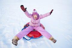 Kind, das im Winterhügel rodelt Stockbild