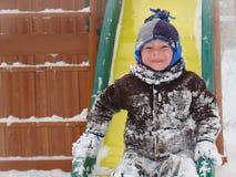 Kind, das im Winterschnee spielt Stockfotos