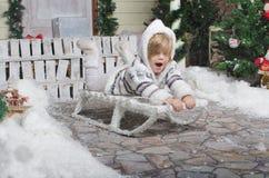 Kind, das im Yard Winterschnee rodelt Lizenzfreie Stockbilder