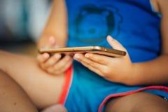 Kind, das intelligentes Telefon spielt stockfoto
