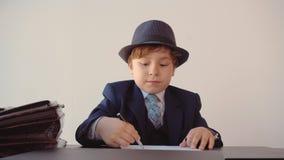 Kind, das Junge wie ein Chef aussieht, macht Schreibarbeit in seinem Büro Erwachsene Lebenparodie, Vorderansicht stock video