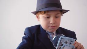 Kind, das Junge wie ein Geschäftsmann aussieht, überprüft Dollar mit Vergrößerungsglas stock video footage