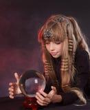 Kind, das Kristallkugel anhält. Stockbild