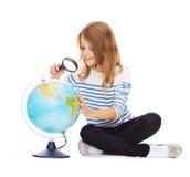 Kind, das Kugel mit Vergrößerungsglas betrachtet Stockbild
