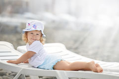 Kind, das lang auf den Strandwagen im Sonnenlicht legt