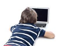 Kind, das Laptop-Computer auf dem Boden verwendet Lizenzfreies Stockbild