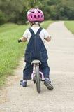 Kind, das lernt, auf sein erstes Fahrrad zu fahren Stockbild