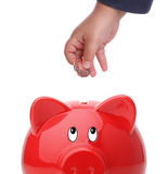 Kind, das Münze in eine piggy Querneigung einsteckt Lizenzfreies Stockfoto