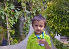 Kind, das Medaille zeigt stockfoto