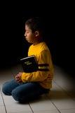 Kind, das mit Bibel betet Lizenzfreie Stockbilder