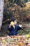 Kind, das mit Blättern spielt Stockbilder