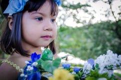 Kind, das mit Blumen stearing ist Stockfoto