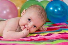 Kind, das mit bunten Ballonen spielt Stockbilder