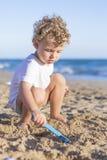 Kind, das mit dem Sand spielt Stockbild