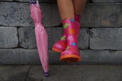 Kind, das mit den Beinen in den Gummistiefeln halten einen Regenschirm sitzt Stockfotos
