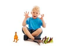 Kind, das mit Dinosaurieren spielt lizenzfreies stockfoto
