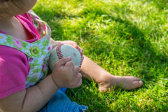 Kind, das mit einem Baseball im Schatten spielt Lizenzfreies Stockfoto