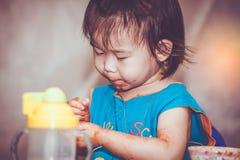Kind, das mit einem befleckten Gesicht isst Tun Sie sie sich Konzept Vintag Stockfotografie