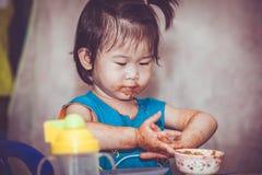 Kind, das mit einem befleckten Gesicht isst Tun Sie sie sich Konzept Vintag Stockfotos