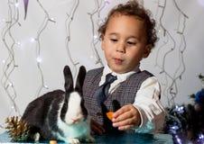 Kind, das mit einem Kaninchen spielt Lizenzfreies Stockfoto