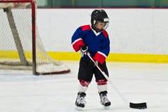Kind, das mit einem Kobold an der Eishockeypraxis eisläuft lizenzfreie stockbilder