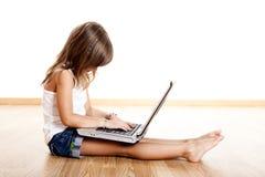 Kind, das mit einem Laptop spielt Stockbilder