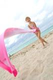 Kind, das mit einem Tuch am Strand spielt Lizenzfreie Stockfotos