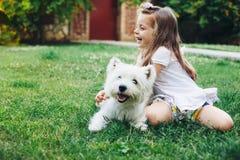 Kind, das mit Hund spielt stockfotos