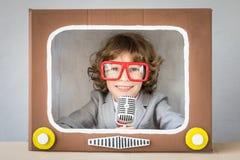 Kind, das mit Karikatur Fernsehen spielt Stockfoto