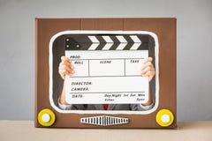 Kind, das mit Karikatur Fernsehen spielt Stockbilder
